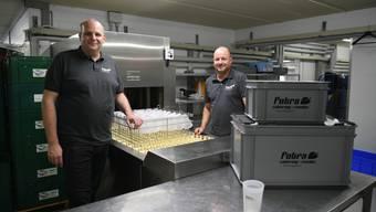 Markus Mehr und Peter Traub vor der neuen 10 Meter langen Abwaschmaschine speziell für Mehrweggeschirr aus Kunststoff.