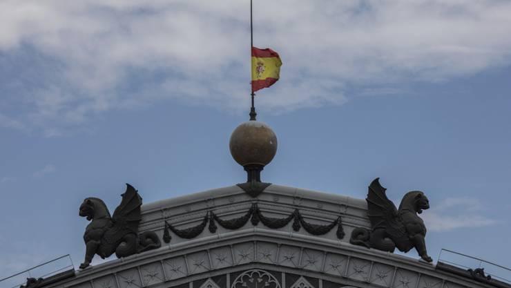 Spanische Fahne auf Halbmast am Dienstag auf dem Dach des Zugbahnhofs Atocha in Madrid. Spanien gedenkt der Corona-Opfer mit einer zehntägigen Staatstrauer.