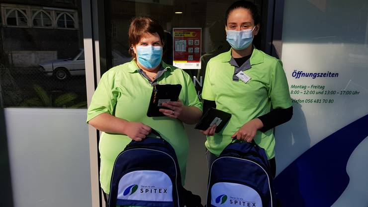 Zwei Mitarbeiterinnen mit Schutzmaske und Tablet vor dem Einsatz.
