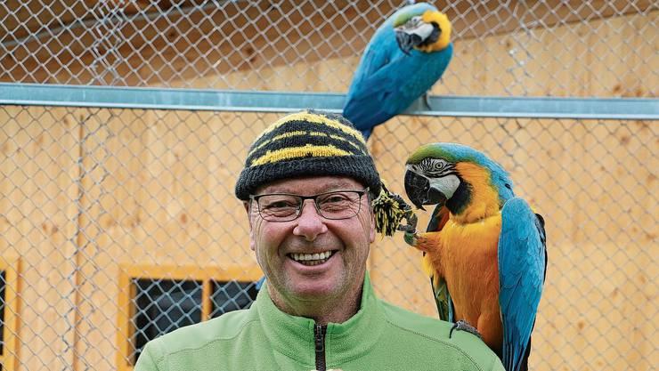 Hat sein Lachen noch nicht verloren: Parkleiter Rolf Lanz und ein Gelbbrustara, der mit ihm Schabernack treibt.