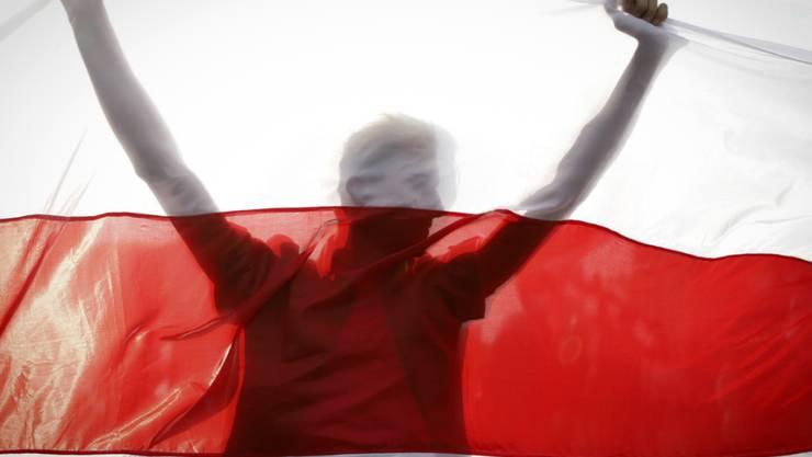 ARCHIV - Ein Demonstrant hält eine historische belarussische Fahne. Trotz eines Großaufgebots an Sicherheitskräften haben Zehntausende Menschen gegen den autoritären Staatschef Lukaschenko demonstriert. Foto: Uncredited/AP/dpa