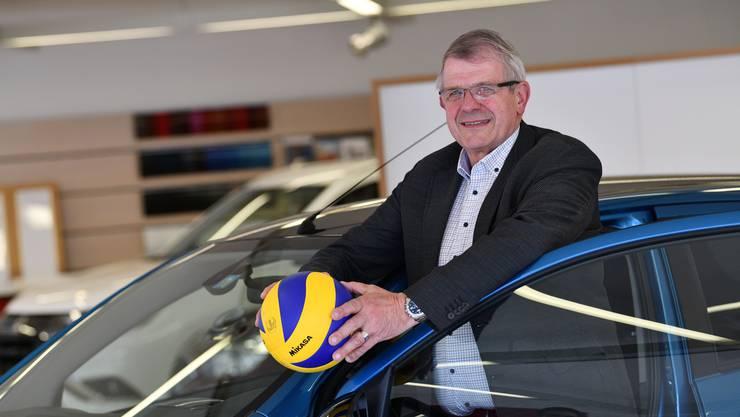 Werner Schmid posiert in seiner Garage in Reinach, wie könnte es anders sein, mit Volleyball und Auto.