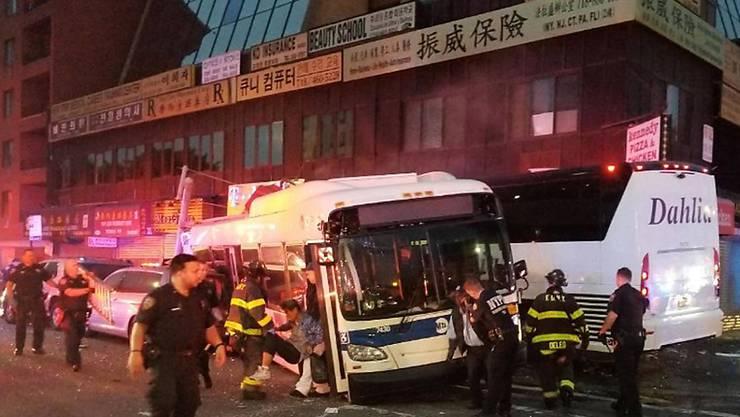 Nach der Kollision zweier Busse in New York sind Polizisten und Feuerwehrmänner im Einsatz.