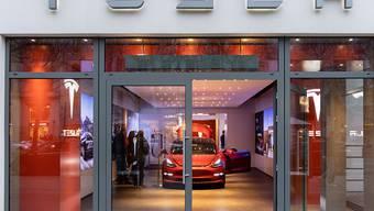 Tesla schliesst doch weniger Läden als angekündigt, erhöht dafür aber die Preise der Fahrzeuge. Im Bild: Tesla-Showroom in Berlin. (Archivbild)