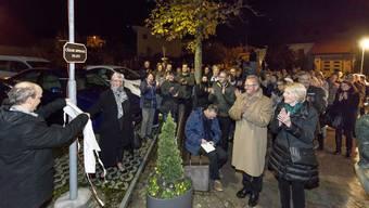 Gemeindepräsident Arno Bürgi und Brigitte Spiegel enthüllen das neue Schild zu Ehren von Cäsar Spiegel.