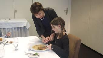 Katrin Künzle, Trainerin für gute Umgangsformen, zeigt der neunjährigen Chanelle, wie sie Messer und Gabel korrekt hält.