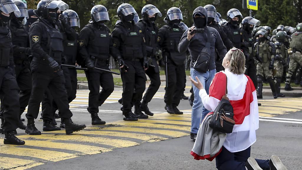 Eine Demonstrantin, die sich eine historische Flagge von Belarus um die Schultern gehängt hat, kniet vor einer Reihe von Polizisten in schwerer Montur auf dem Boden. Foto: -/TUT.by via AP/dpa