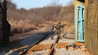 Ein Soldat öffnet ein Grenztor zwischen Nord- und Südkorea, damit ein Zug mit südkoreanischen Experten passieren kann. Die Delegation soll den Zustand des Schienennetzes prüfen, damit später die zwischenstaatlichen Eisenbahnverbindungen wieder aufgenommen werden können.