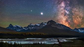 Der helle Jupiter und Saturn (links)  unter der Milchstrasse über dem Saskatchewan River in den USA.