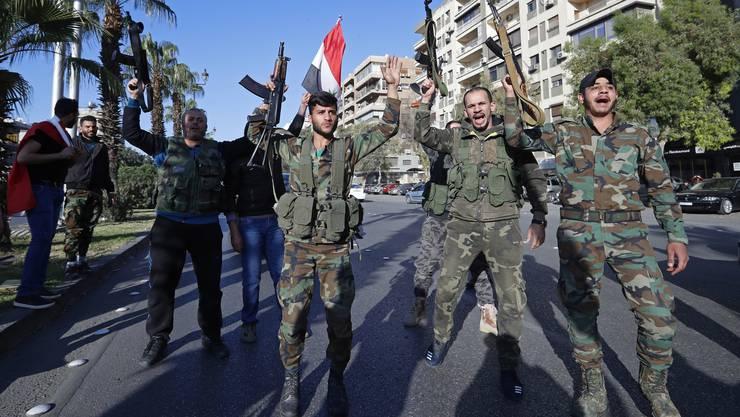 Syrische Soldaten halten ihre Waffen in die Luft. Sie demonstrierten gegen US-Präsident Trump nach dem militärischen Angriff auf Syrien der Westmächte.