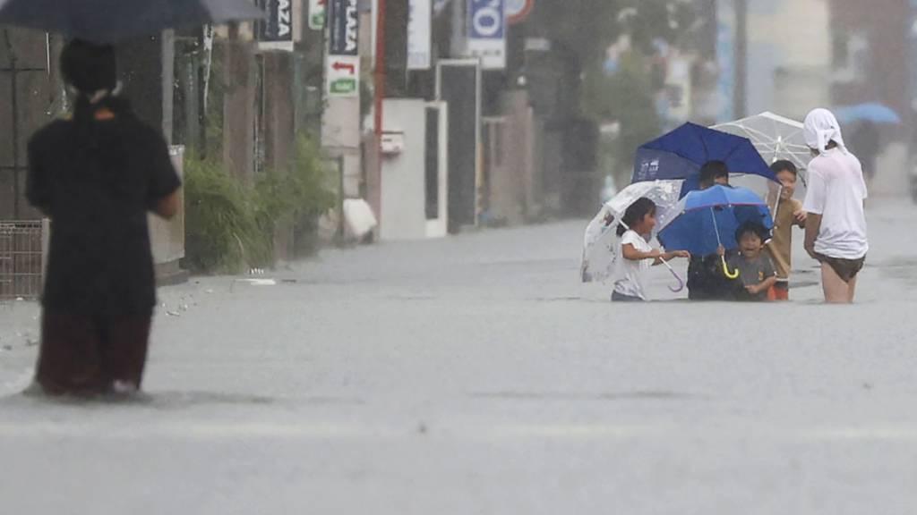 Menschen waten durch eine überflutete Straße in Kurume, Westjapan. Sintflutartige Regenfälle suchten den Südwesten Japans seit Freitag heim und forderten mindestens sechs Todesopfer. Nach einer Unterbrechung regnete es am Montagmorgen (Ortszeit) auf der südwestlichen Hauptinsel Kyushu erneut stark. Foto: Kyodo News/via AP/dpa - ACHTUNG: Nur zur redaktionellen Verwendung und nur mit vollständiger Nennung des vorstehenden Credits