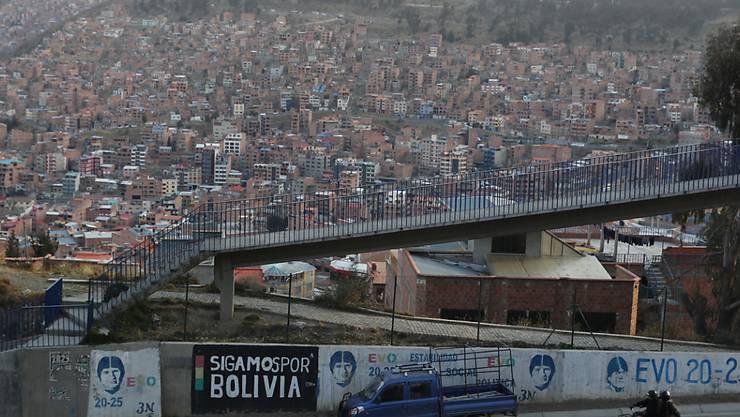 Ein Auto fährt an Wahlplakaten des ehemaligen bolivianischen Präsidenten Evo Morales vorbei, die an einer Wand gemalt sind. In Bolivien finden am 18.10.2020 Präsidentschafts- und Parlamentswahlen statt. Foto: Juan Karita/AP/dpa
