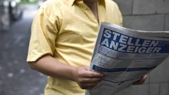 Ein Arbeitsloser liest den Stellenanzeiger (gestellte Aufnahme)