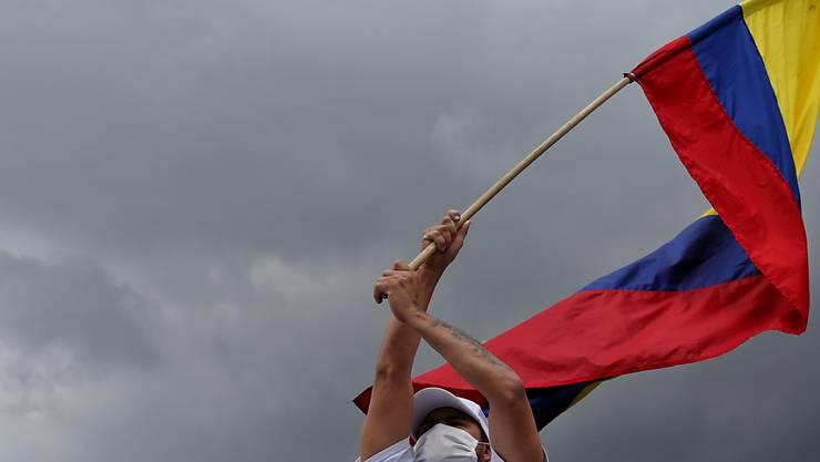 Ein Demonstrant schwenkt während eines «Marsches für das Leben und den Frieden» von Ex-Kämpfern der Farc-Guerilla die Fahne von Kolumbien. Foto: Camila Diaz/colprensa/dpa