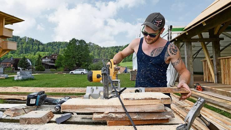 Einer von fast 3000 Helfern: Angelo Knedel sägt in Rikon Holz für die Bar. Schon am ersten Festwochenende werden rund 20 000 Personen erwartet.