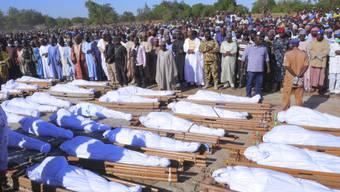 ARCHIV - Menschen stehen bei einer Beerdigung vor den Leichen der Personen, die bei einem Angriff ums Leben gekommen sind. Im Nordosten Nigerias sind der UN zufolge bei einem «brutalen» Angriff mindestens 110 Menschen getötet worden. Foto: Jossy Ola/AP/dpa