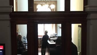 Bundesanwalt Michael Lauber (stehend, Mitte) gestern vor Zimmer 3 im Parlamentsgebäude. Abgeschirmt durch Personenschützer, die mit dem Rücken zur Glaswand stehen.
