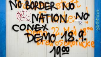 Ein Schriftzug an einem Container ruft zu einer Demo gegen die Truppenübung Conex 15 auf.