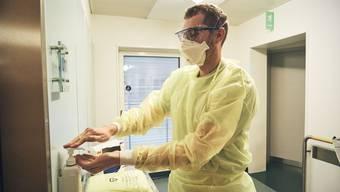 Händehygiene bleibt das A und O im Kampf gegen Corona. Das Spitalpersonal trägt zusätzlich Maske, Schutzbrille und einen speziellen Anzug.