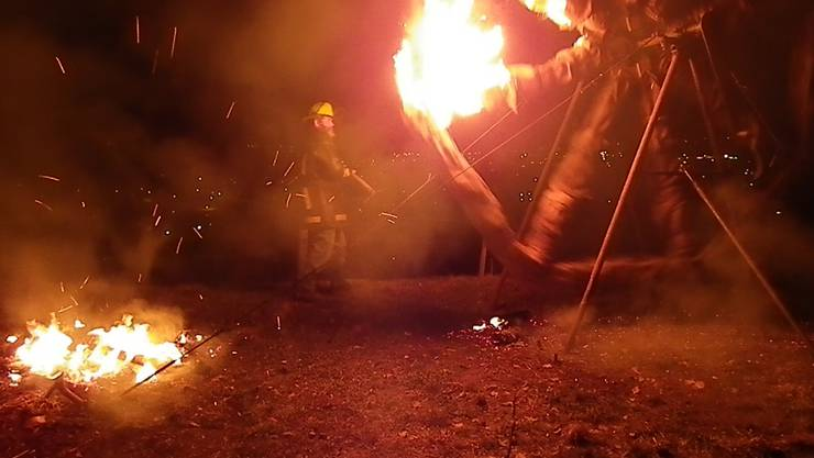 Der grosse Augenblick naht: Sepp Hauswirth entnimmt dem nahen Feuer brennende Scheiter und zündet mit diesen das sich in Drehung befindliche Rad an.