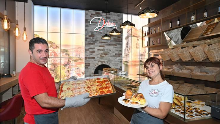 Der Pizzaiolo Andrea Caruso präsentiert eine frisch gebackene Pizza. Die Geschäftsführerin Margherita Alioto zeigt die portugiesische Patisserie.