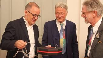 Stadtpräsident Hanspeter Hilfiker erhält von Andreas Röthlisberger und Vital Baldinger (v.l.) eine Bundeshausplakette.