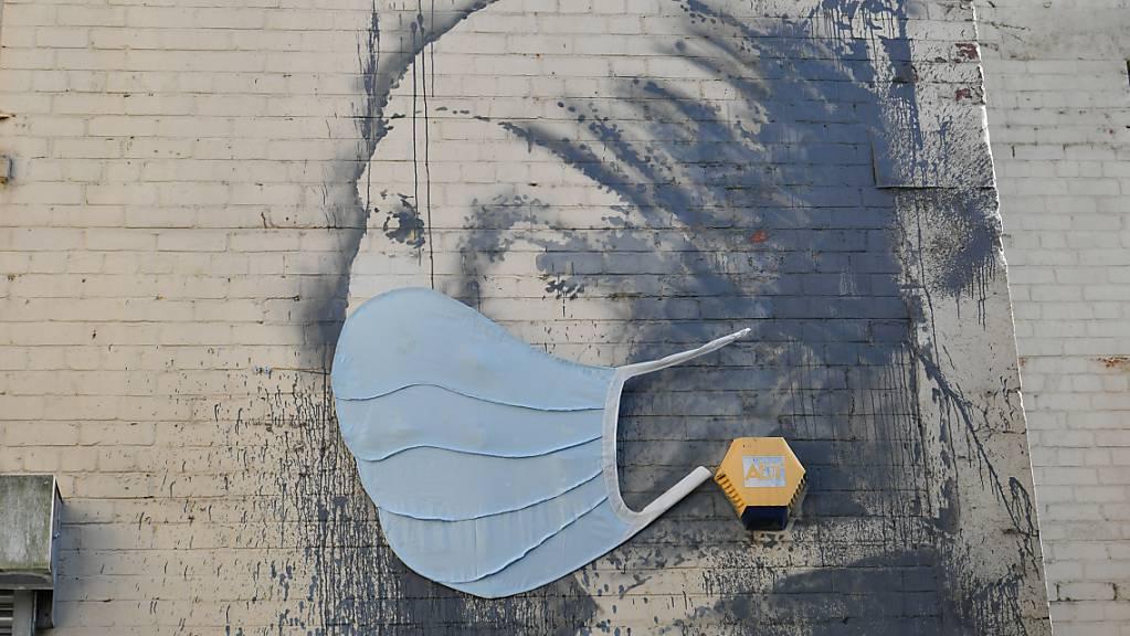 ARCHIV - Das Wandgemälde «Das Mädchen mit dem Perlenohrring», das von dem britischen Streetart-Künstler Banksy stammen soll, auf dem Hanover Place, hat als Reaktion auf die Coronavirus-Pandemie eine Gesichtsmaske bekommen. Foto: Ben Birchall/PA Wire/dpa - ACHTUNG: Nur zur redaktionellen Verwendung im Zusammenhang mit der aktuellen Berichterstattung und nur mit vollständiger Nennung des vorstehenden Credits