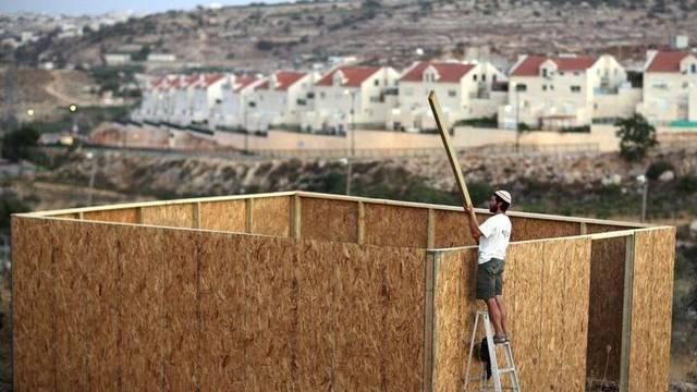 Ein israelischer Siedler baut in der Nähe von Hebron an seinem Haus (Archivbild)