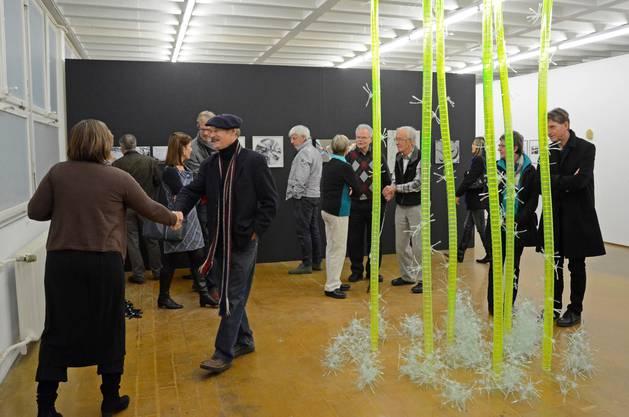 """Vernissage im Kunstraum Baden: Claudia Spinelli begrüsst Rudolf Ottischnig. Im Hintergrund zahlreiche Kunstinteressierte, unter ihnen Künstler Beat Buri, der in """"Truffes & Trouvailles"""" ausstellt."""