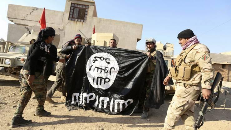 Irakische Soldaten mit einer konfiszierten IS-Flagge. (Archivbild)