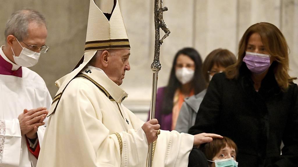 ARCHIV - Papst Franziskus (M) streicht über den Kopf eines Jungen, als er in die Basilika Sankt Peter kommt, um die Christmette zu feiern. Der Papst leidet an Ischias-Schmerzen und sagt deswegen nach Angaben des Vatikans zwei Termine zum Jahreswechsel ab. Foto: Vincenzo Pinto/AFP POOL/AP/dpa