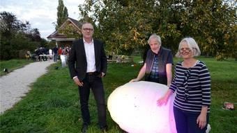 Vernissage-Redner Matthias Anderegg, der Künstler Alois Herger mit einem seiner Leuchtobjekte, sowie Bea Beer, Präsidentin des Quartiervereins Weststadt, freuen sich über die Premiere von «à la folie» beim Lusthäuschen.