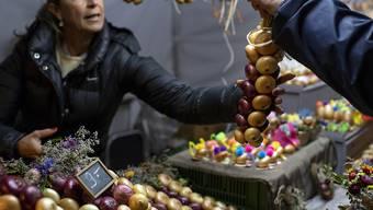 Unzählige Zwiebelzöpfe, viele von ihnen mit kleinen Blumen verziert, werden am Berner Zibelemärit angeboten.