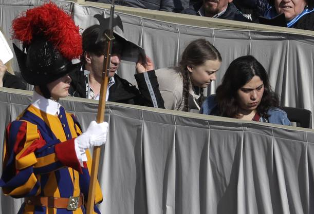 Swedish teenage environmental activist Greta Thunberg, second from right, crouches to get to her seat during Pope Francis' weekly general audience in St. Peter's Square, at the Vatican, Wednesday, April 17, 2019. (AP Photo/Gregorio Borgia)
