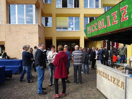 Besucher warten vor dem Altbau des Schulhauses Allmend auf die Einweihung.