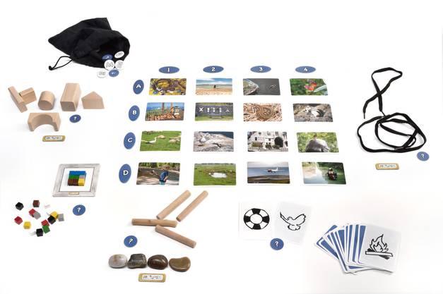 """Bauklötze, Schnürsenkel, Symbol-Karten und mehr. Die insgesamt fünf in """"Pictures"""" enthaltenen Material-Sets könnten auf den ersten Blick kaum unterschiedlicher sein. Trotzdem dienen sie alle demselben Zweck: Mit ihnen sollen die Spielenden Foto-Motive so darstellen, dass die anderen diese in der großen Gesamtauslage wiederfinden können. Je nach Aufgabe und Material ist das gar nicht mal so einfach, denn es erfordert kreative Ideen und Abstraktionsvermögen. Außerdem muss der Überblick über die anderen Motive der Auslage gewahrt werden, damit man nicht versehentlich doppeldeutig werkelt. Wenn alle Spielenden mit ihren Kreationen zufrieden sind, folgt das gegenseitige Erraten mit Punktevergabe. Anschließend wird durchgetauscht, sodass jeder jedes Material-Set einmal ausprobieren kann."""