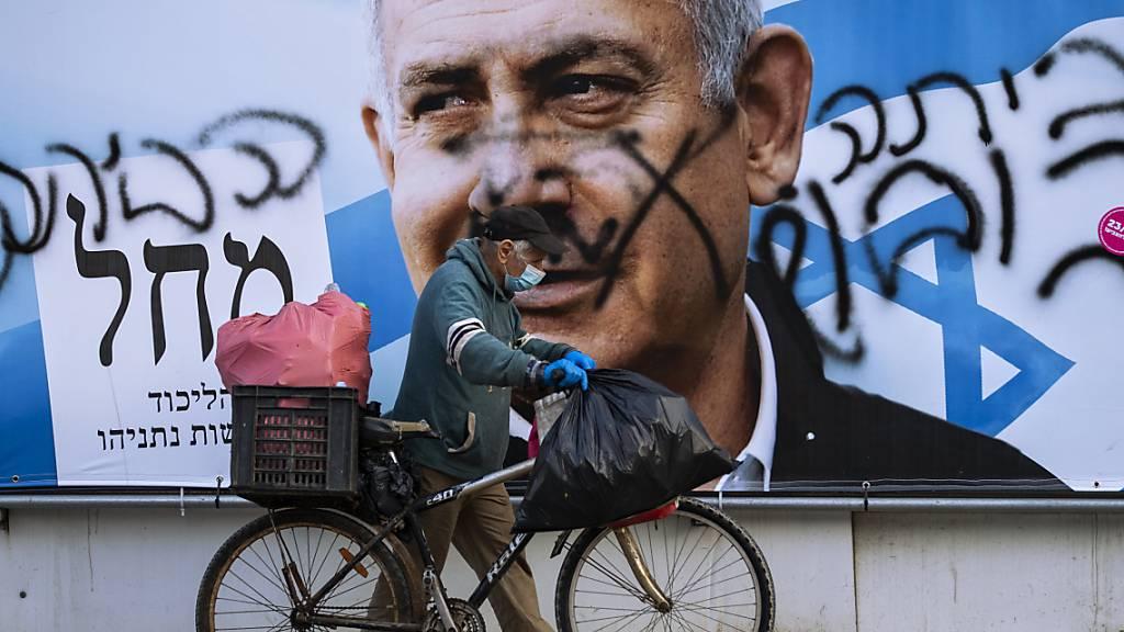 Ein Mann schiebt ein Fahrrad an einem beschmierten Wahlkampfplakat der Likud-Partei mit dem Bild des Parteivorsitzenden und Israels Ministerpräsidenten Netanjahu vorbei. Foto: Oded Balilty/AP/dpa