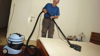 Milbenjäger Roman Zigerli demonstriert, wie er Matratzen aussaugt.