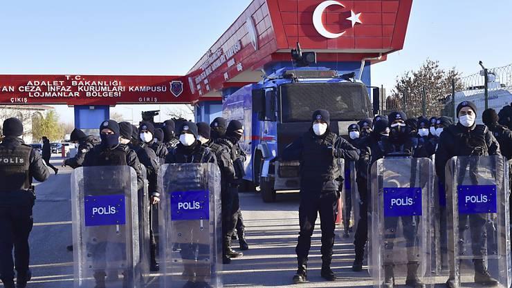 Polizeibeamte mit Mund-Nasen-Schutz und Schutzausrüstung stehen Wache am Eingang eines Luftwaffenstützpunktes, nahe eines Gerichtsgebäudes. Mehr als vier Jahre nach dem Putschversuch in der Türkei hat ein Gericht Urteile gegen Hunderte Beteiligte gefällt. Foto: Uncredited/AP/dpa