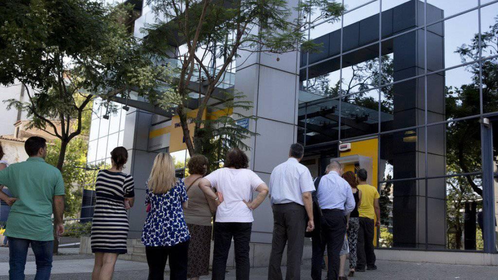 Warteschlange vor einem Geldautomaten einer Filiale der Piraeus Bank in Athen. (Archivbild)