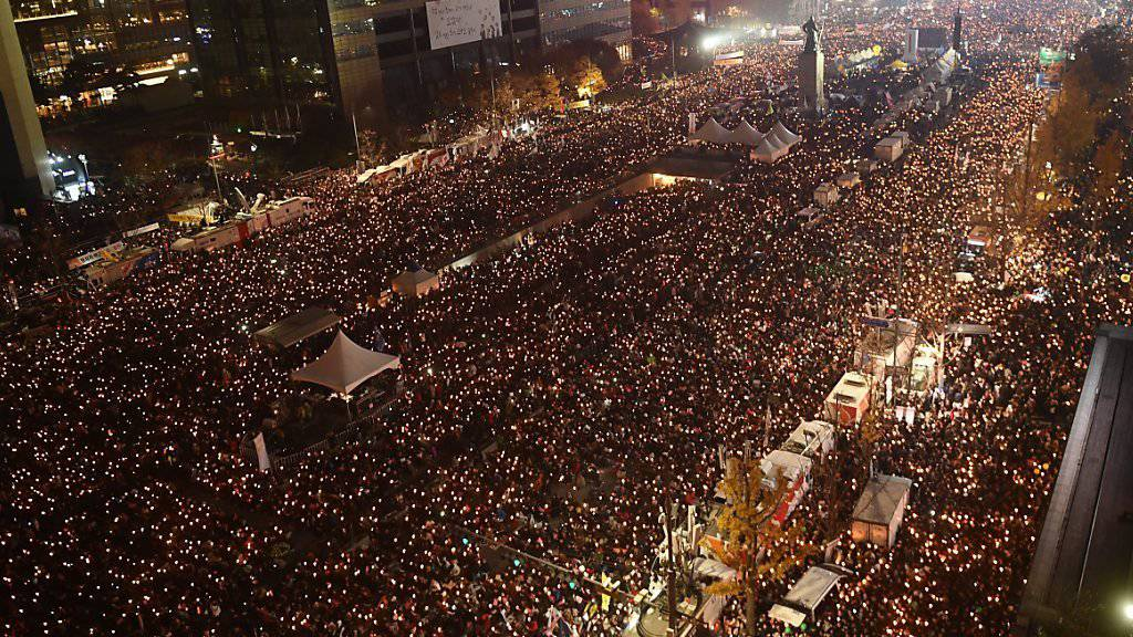 In Südkoreas Hauptstadt demonstrieren Tausende gegen Präsidentin Park Geun-Hye. Mit Kerzen gingen die Menschen auf die Strasse und forderten den Rücktritt von Park.