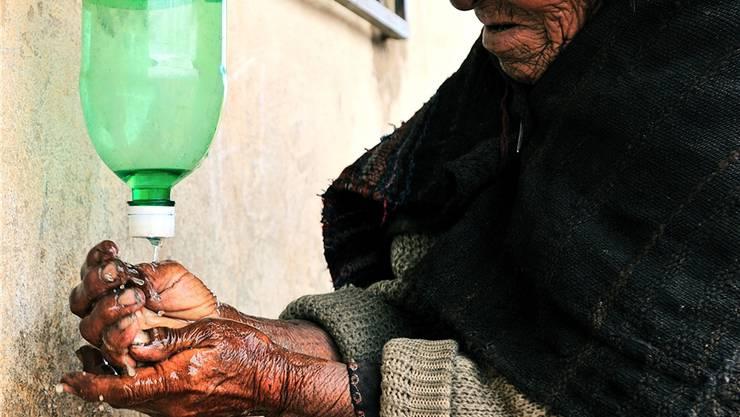 Hygiene ist wichtig, aber Wasser ist ein knappes Gut: mit diesen mobilen Händewasch-Stationen waschen sich die Frauen mit wenig Wasser die Hände (Frau aus Choquellusta, © Fundación SODIS).