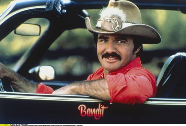 """Der US-amerikanische Schauspieler Burt Reynolds sitzt in seiner Rolle in dem Spielfilm """"Ein ausgekochtes Schlitzohr"""" mit einem Stetson auf dem Kopf im Auto. Undatiertes Foto."""