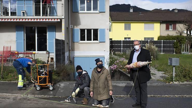"""Schnüre statt Glasfasern: Die Konzeptkünstler Frank (Mitte) und Patrik Riklin sowie Stadtpräsident Ruedi Mattle (rechts) bei der Verlegung des """"Analogen Fadennetzes""""."""