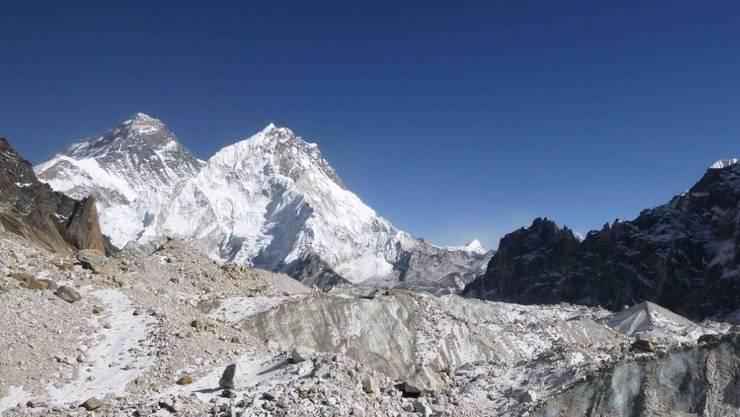 Blick auf den Mount Everest (links im Hintergrund). Im Vordergrund ist der Changri Nup, ein typischer, teils mit Geröll bedeckter Gletscher zu sehen.