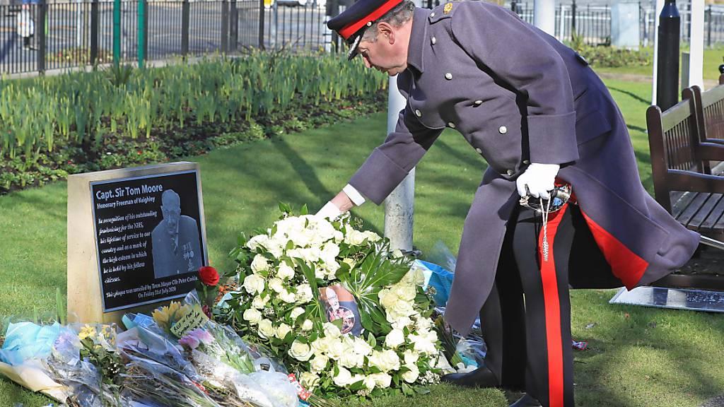 David Pearson, Deputy Lieutenant für West Yorkshire, legt am Tag der Beerdigung von Kapitän Sir Thomas Moore (Captain Tom), der an den Folgen einer Corona-Infektion gestorben ist, einen Kranz aus 200 weißen Rosen an dessen Gedenktafel nieder. Foto: Danny Lawson/PA Wire/dpa
