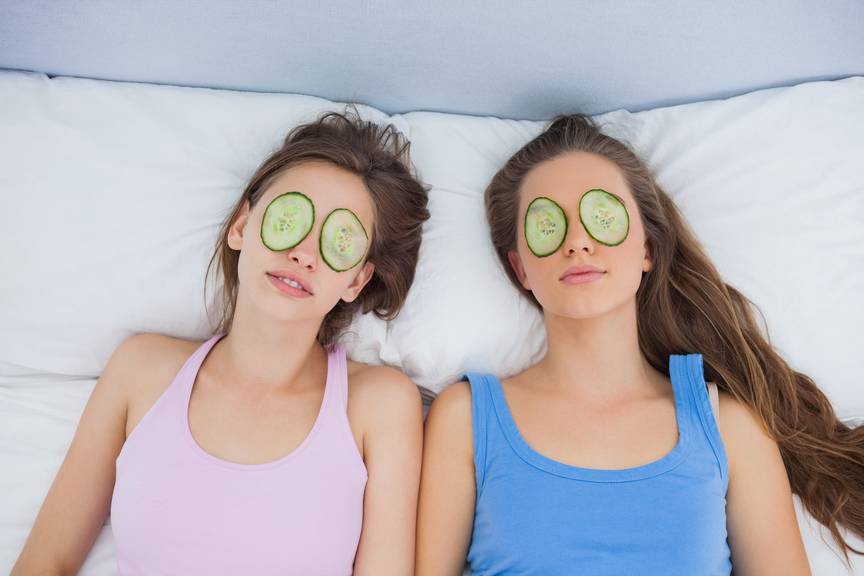 Friends relaxing in bed with cucumber on eyes at sleepover