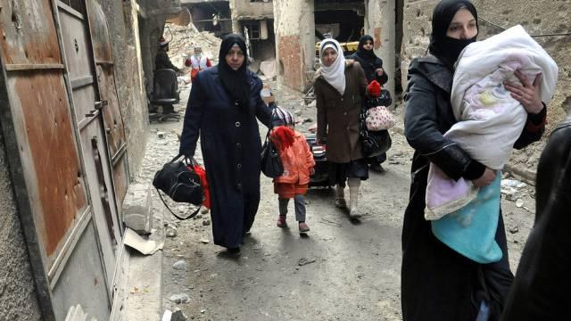Frauen fliehen mit ein paar Habseligkeiten aus Jarmuk (Archiv)