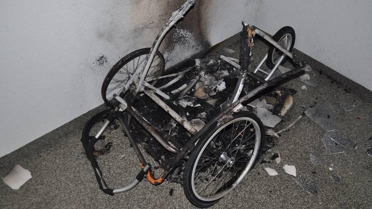 Der ausgebrannte Kinderwagenanhänger