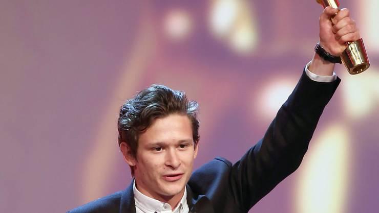 Joel Basman mit der Trophäe des deutschen Filmpreises. Die goldene Lola erhielt er für die beste Nebenrolle.